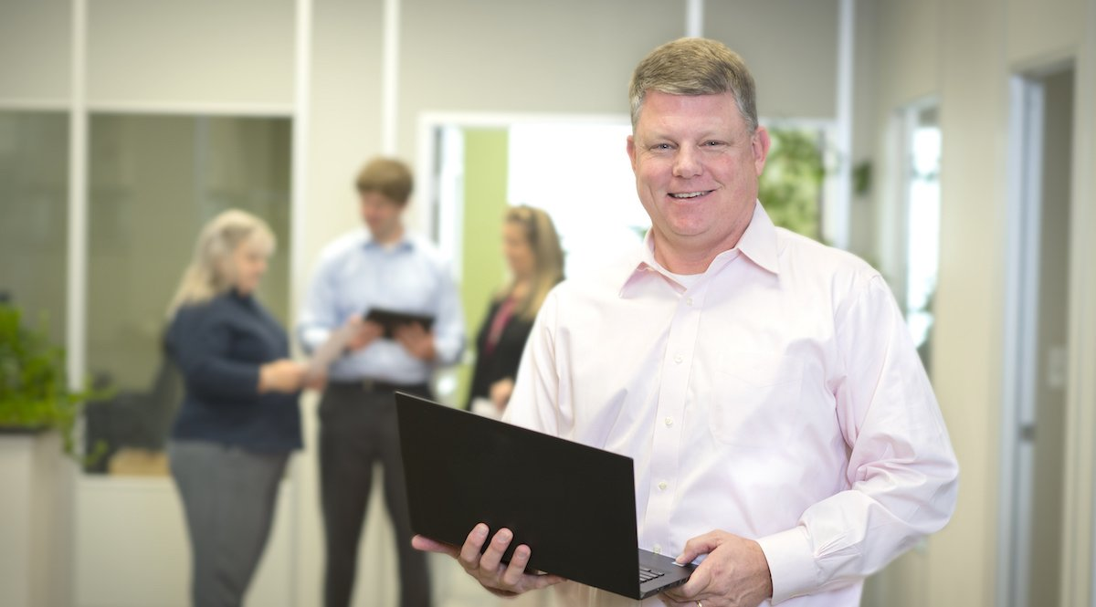 Magnolia Financial employee holding laptop in office